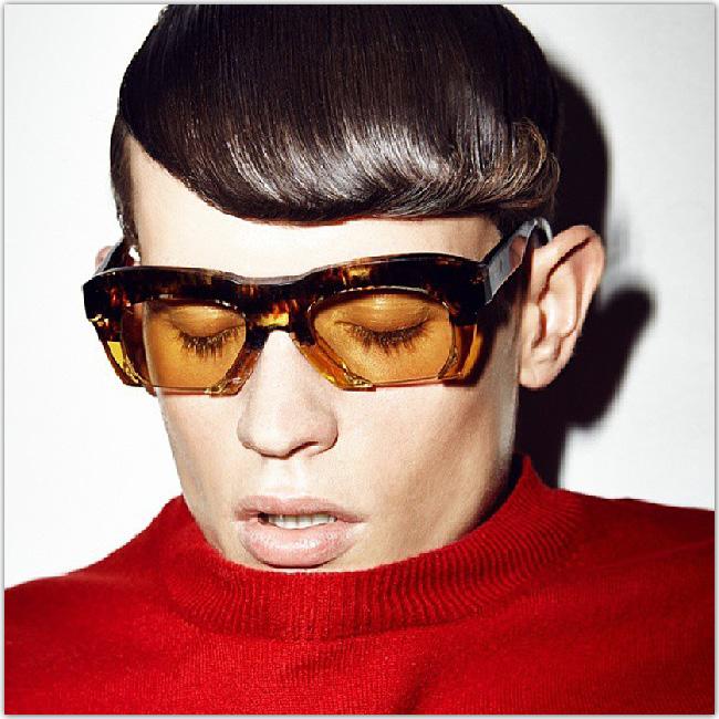 Personne avec un pull rouge et des lunettes teintées