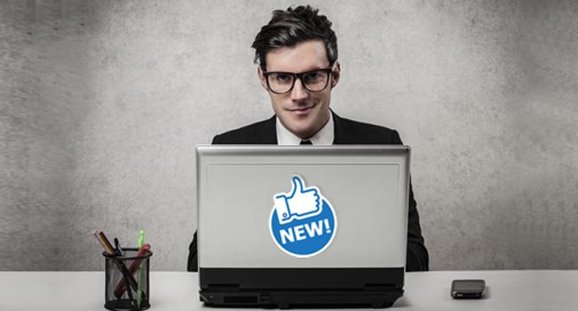 Homme sur son ordinateur qui souris avec un autocollant Facebook