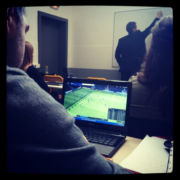 personne qui regarde un match de foot pendant un cours