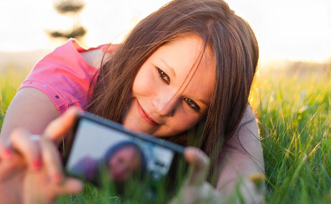 Femme qui prend une photo allongée dans l'herbe