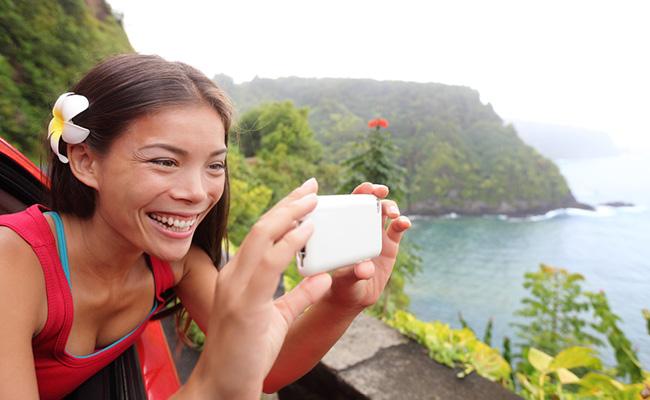 Femme souriante prend en photo un paysage