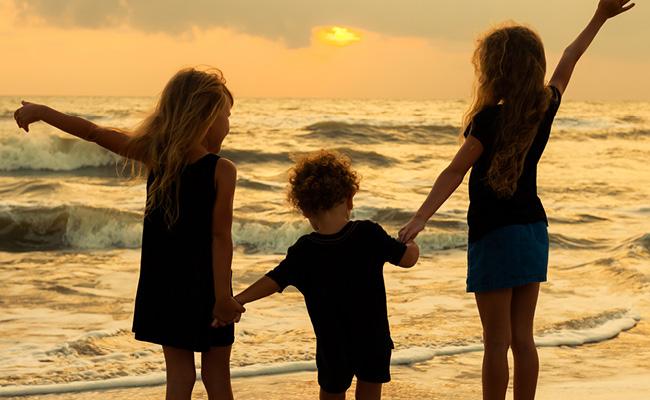 3 enfants au bord de la plage au coucher du soleil