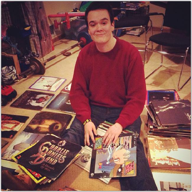 Homme assis dans une collection de vinyles