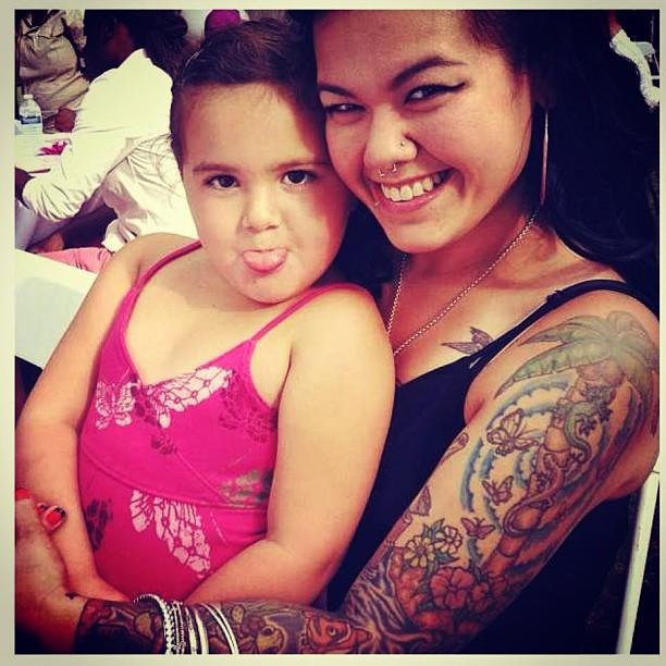 Femme tatouée qui tient un enfant dans ses bras
