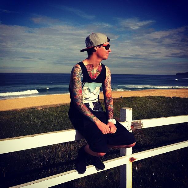 Jeune homme tatoué qui regarde l'horizon