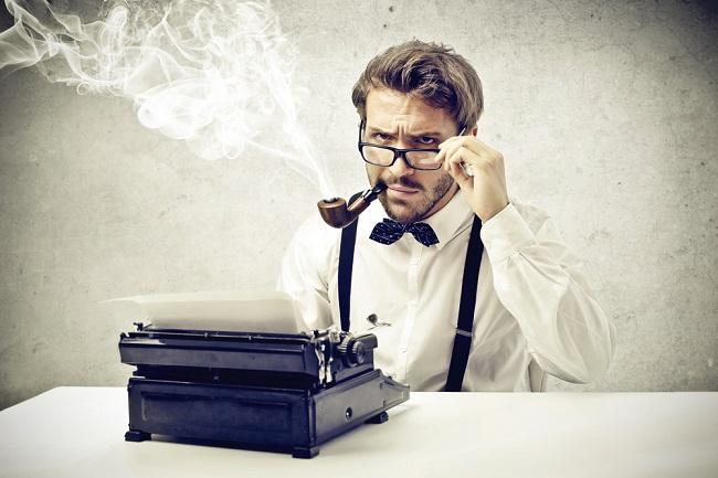 Homme pensif devant une machine à écrire