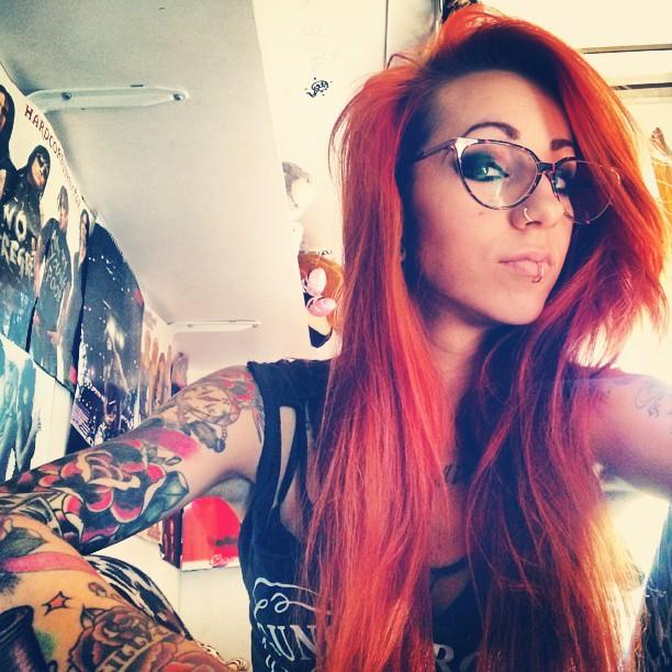 Jeune femme rousse tatouée sur les bras