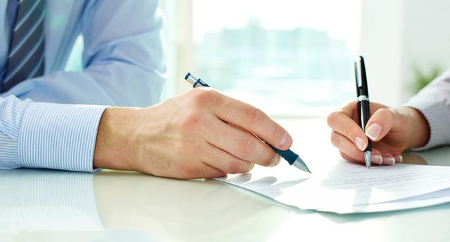Personne en train d'écrire sur une feuille