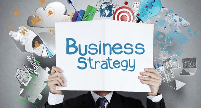 Homme d'affaires derrière une pancarte business strategy