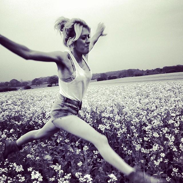 Femme qui saute dans un champ en noir et blanc