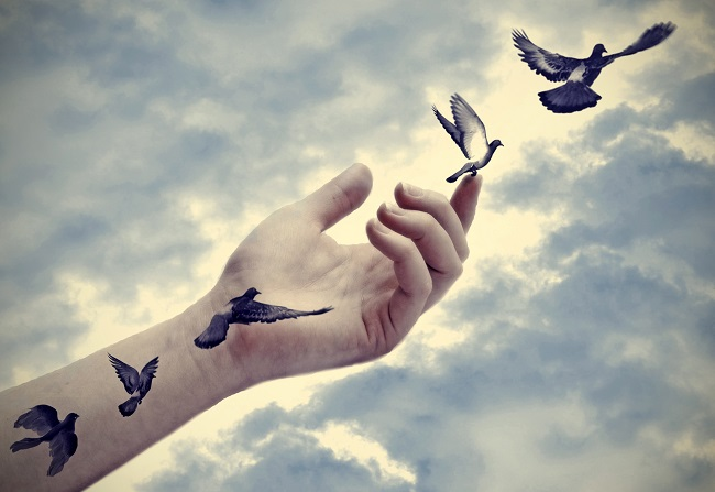 Tatouages d'oiseaux sur un main qui prennent leur envol