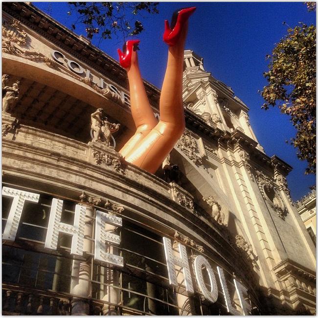 Photo d'un bâtiment d'où sortent des jambes de femmes