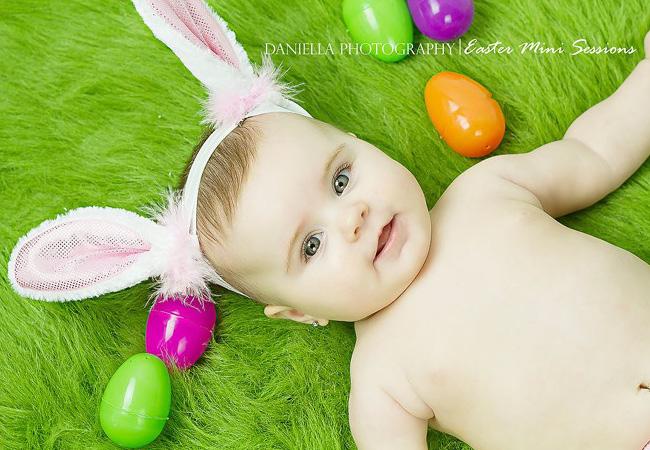 Bébé avec des oreilles de lapin allongé entre des œufs de Pâques
