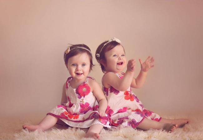 Deux petites filles en robe à fleurs dos à dos