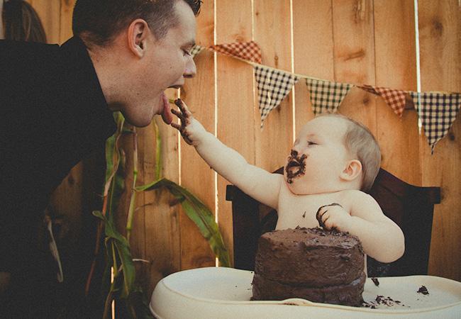 bébé qui mange un gâteau au chocolat avec les mains en propose à son père