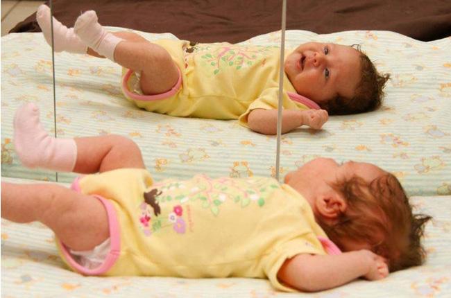 bébé en grenouillère jaune qui se regarde dans le miroir