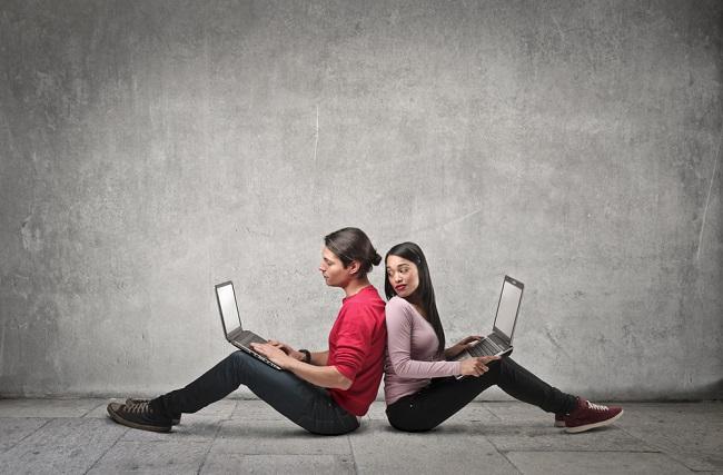 Deux personnes dos à dos qui écrivent sur leur PC