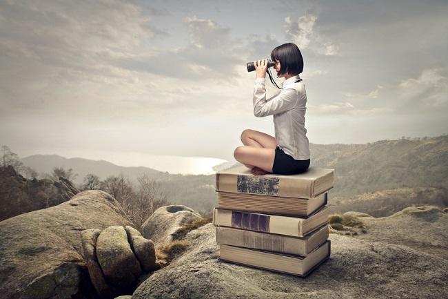 Jeune fille assise sur des livres qui regarde dans des jumelles