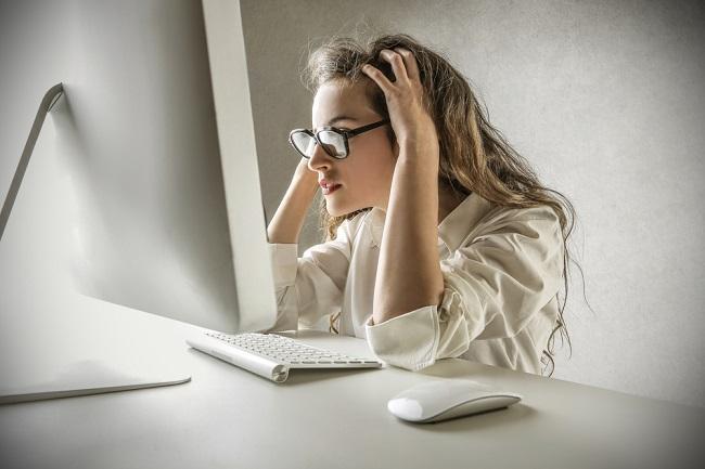 Jeune fille perplexe devant un ordinateur